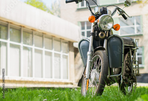 A moped-style e-bike parked on the grass