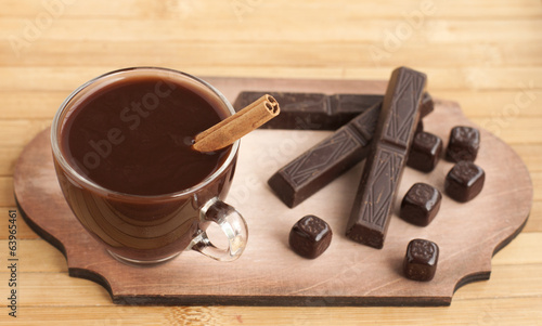 Hot chocolate with cinnamon and spices in a glass cup and chocol