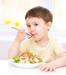 Cute little boy is eating vegetable salad