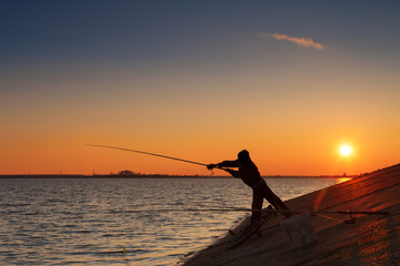 Silhouette of fisherman fishes on river bank against a sunset