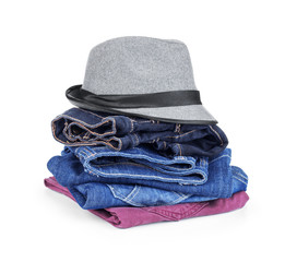 stack of jeans with a hat on an isolated white background