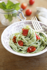 Spinach pasta with tomatoes, mint and goat cheese