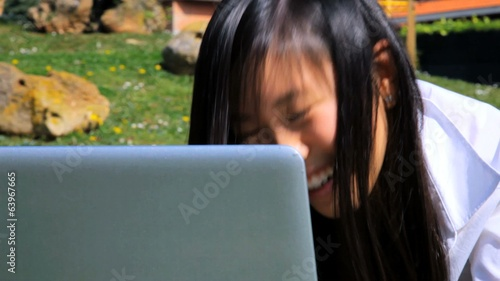 Cute asian woman having fun chatting with pc