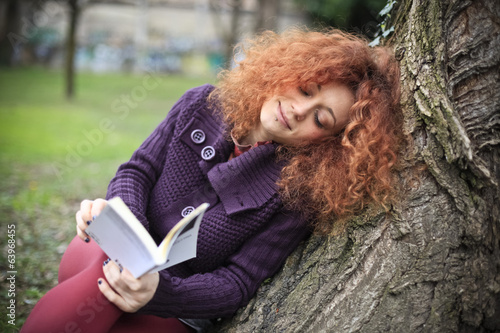 Student reads a book at the park