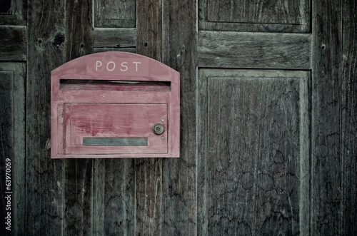Grunge red wooden mail box on grunge wooden wall