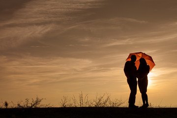 Silhouette of pregnant woman and a man in the sunset