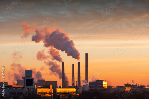 Winter scenic of power plant with a burning yellow sky behind