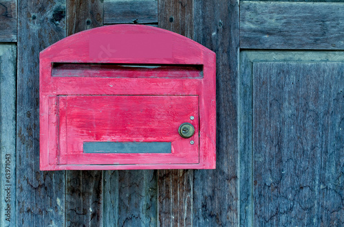 red wooden mail box on grunge wooden wall