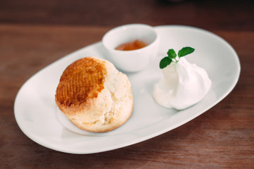 A delicious scone with clotted cream and jam on white plate