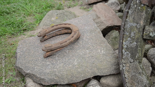 hand put into a pile horseshoes on stone outdoor