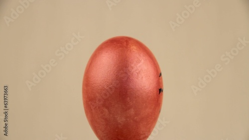 Pink egg rotates and shows contented face, video