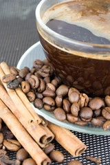 a cup of coffee with coffee beans and cinnamon sticks