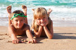 Two happy children on beach, sea in background.