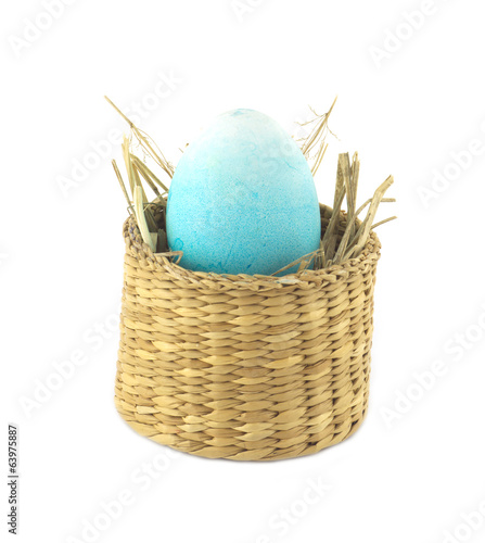 Color Easter egg in in small brown basket isolated
