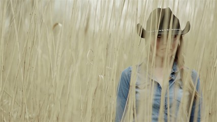 Girl in a cowboy hat standing in the field of grain