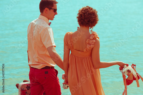 Summer vacation concept. Married hipsters walking on beach