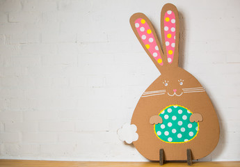 Rabbit made from organic paper on a white wall. Decoration