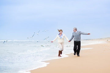 Happy mature couple running at a beautiful winter beach