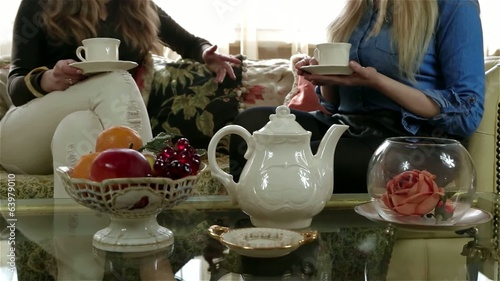 Elegant tea set on the table, female friends on the background