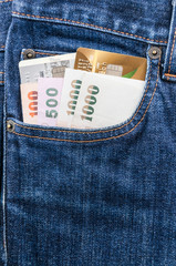 dollars & credit card in blue jean pocket