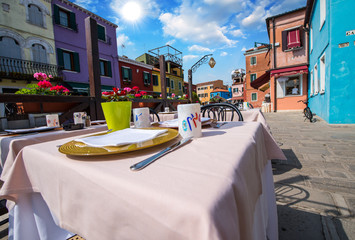 Burano, Italy. Prepared table with classic colourful buildings i