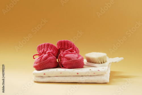 Baby booties, combs and diapers on a beige background