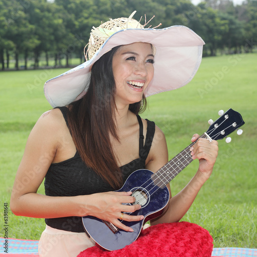 Asian woman playing Ukulele