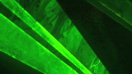 Green laser light flashing on a dark background.