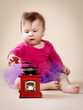 Little baby girl with coffee grinder wearing tutu skirt