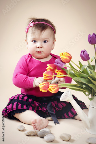 Little baby girl with spring bunch of tulips
