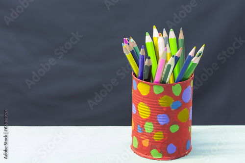 Colorful pencils in pail isolated on black