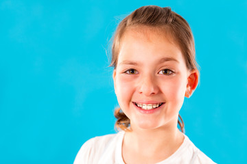Young girl with dental braces on her teeth isolated on blu