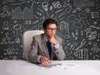 Businessman sitting at desk with business scheme and icons