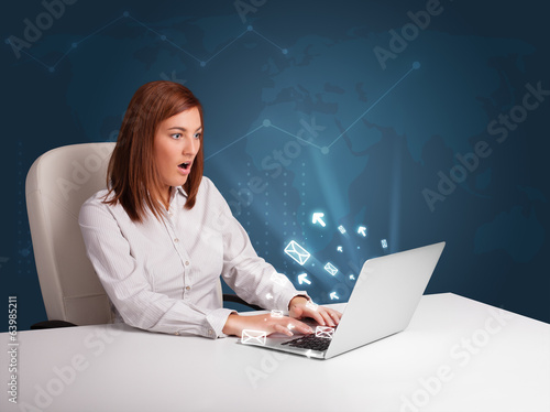 Young lady sitting at dest and typing on laptop with message ico