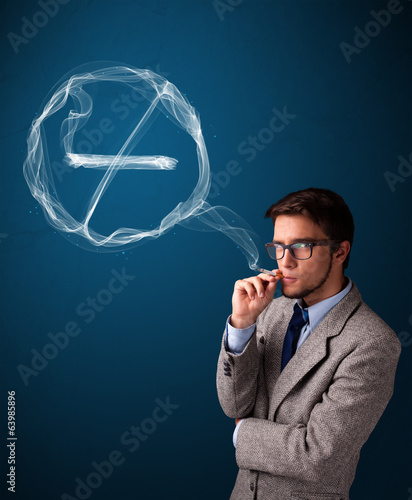Young man smoking unhealthy cigarette with no smoking sign