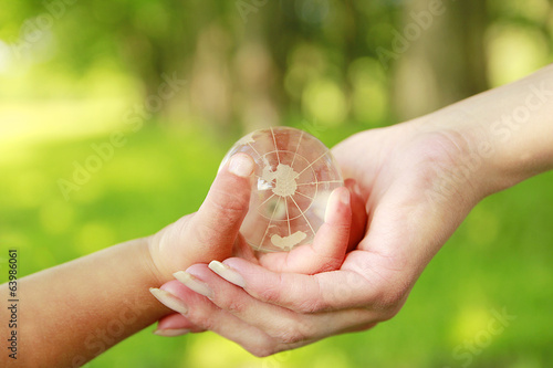 glass globe in the hand of a parent and child