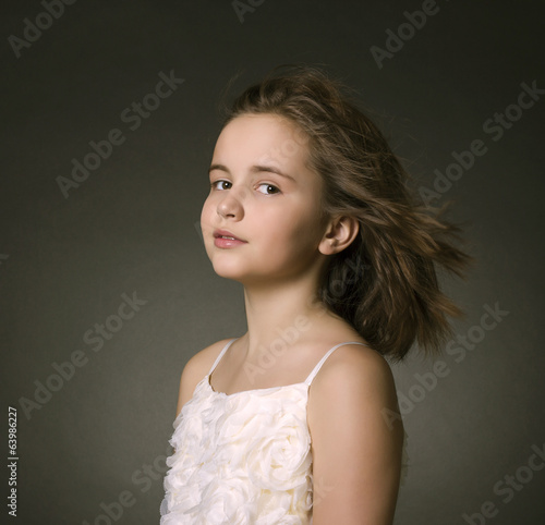 Portrait of a young girl on a dark background.