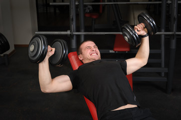 Young man doing Dumbbell Incline Bench Press workout in gym