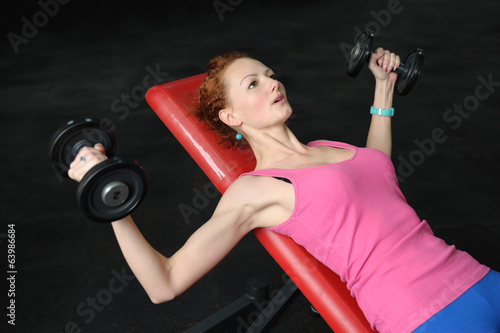 canvas print picture Young girl doing Dumbbell Incline Bench Press workout