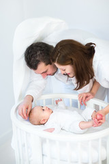 Happy young parent looking at their baby son in white round crib