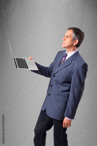 Handsome businessman holding modern laptop