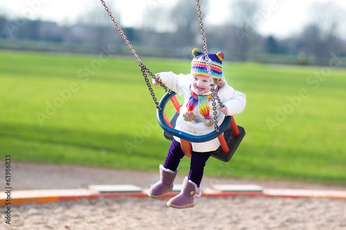 Happy laughing toddler girl swinging on a playground