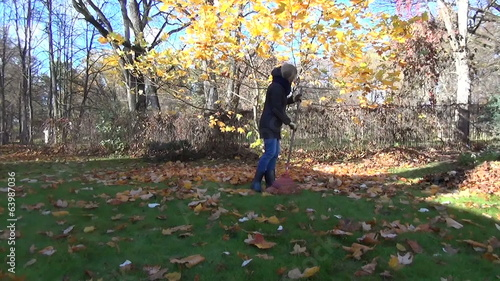 student raking with rake autumn leaves in grandmother garden