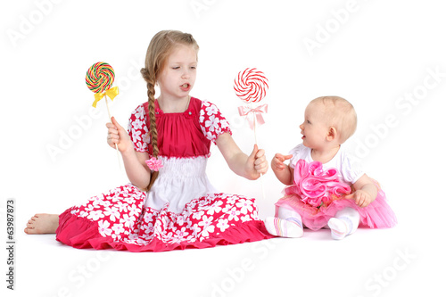 adorable little two sisters 8 year and  11 month old  with candy