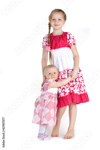 adorable little two sisters 8 year and  11 month old on white ba