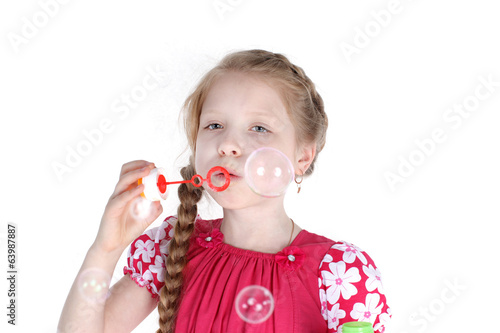 little girl 8 years old blowing soap bubbles