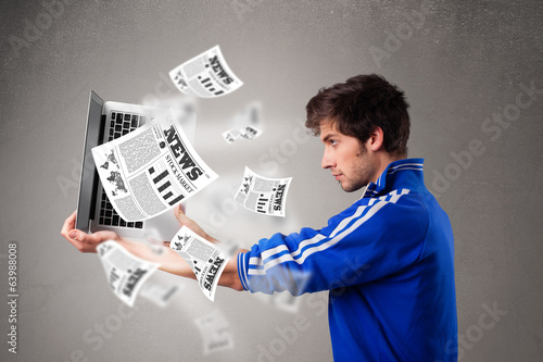 Young man holding a laptop and reading the explosive news