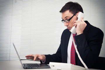 businessman speaking on phone, sitting at desk, looking at lapto