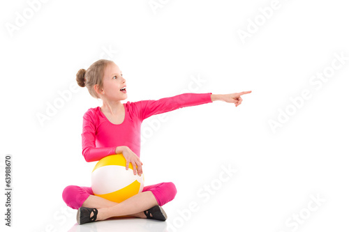 Shouting gymnastics girl with a ball pointing.