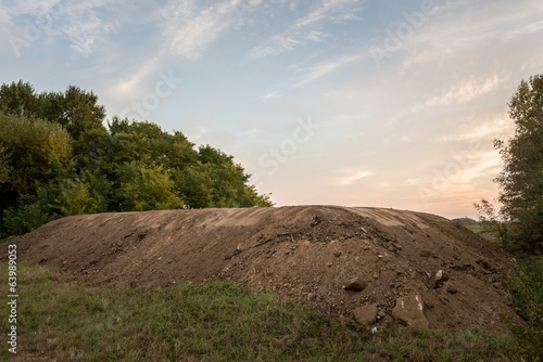Large pile of soil under blue sky